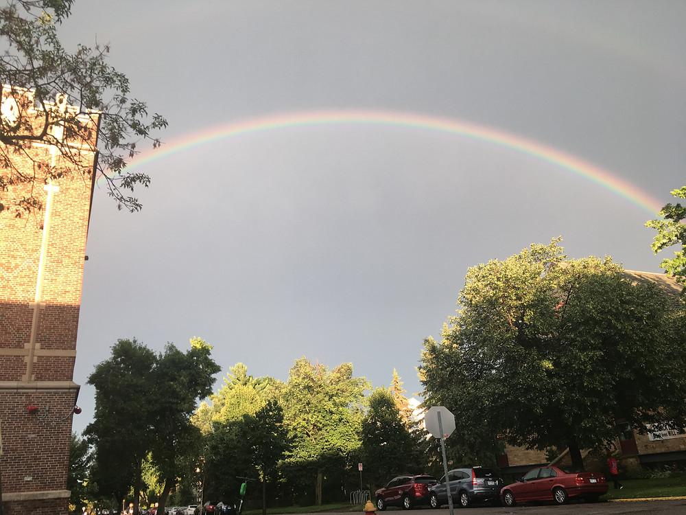 rainbow above street buildings cars below