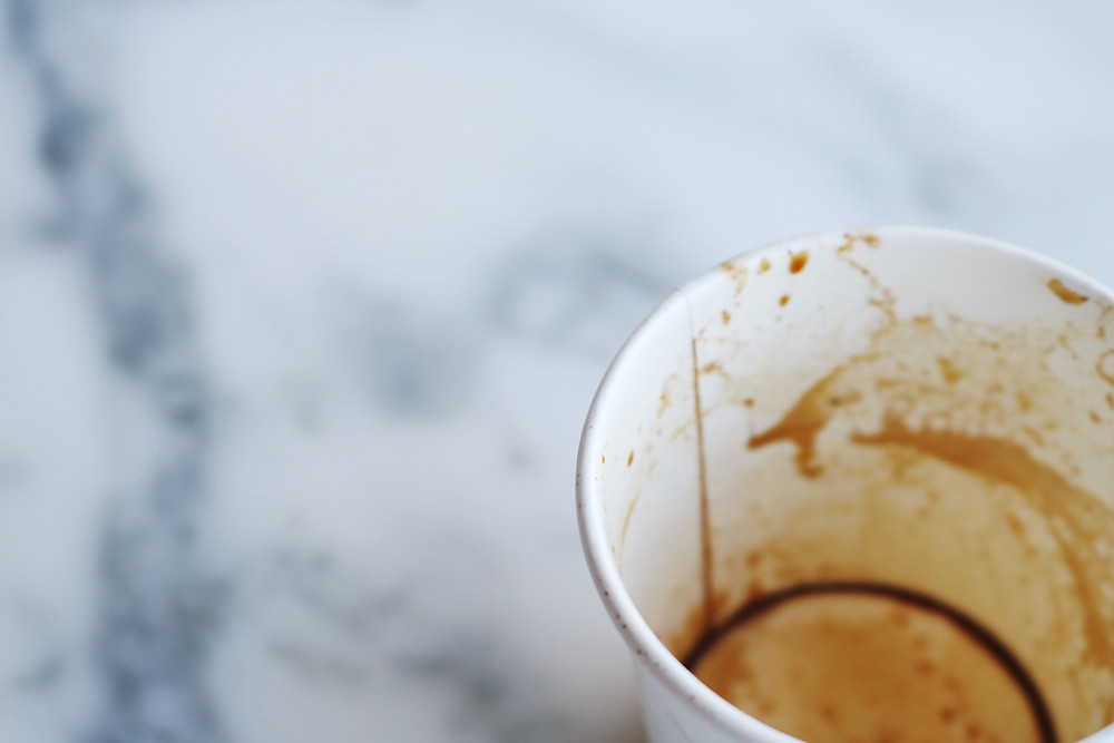 Empty paper cup with coffee on marble table