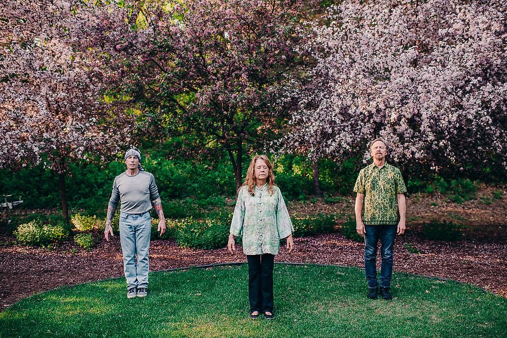 Two men one woman standing under flowering trees meditating