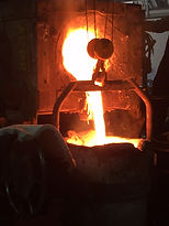 metal pouring into a ladle at the foundry
