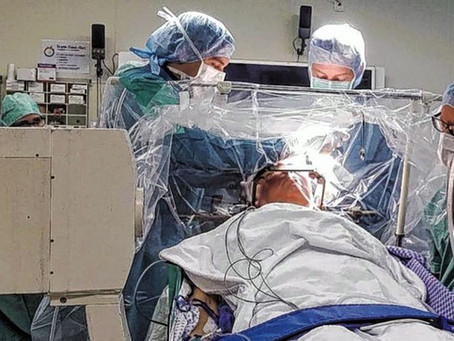 WORLD'S FIRST DEEP BRAIN SURGERY USING HYPNOSIS INSTEAD OF ANAESTHETIC CURES ELDERLY PATIENT'S T