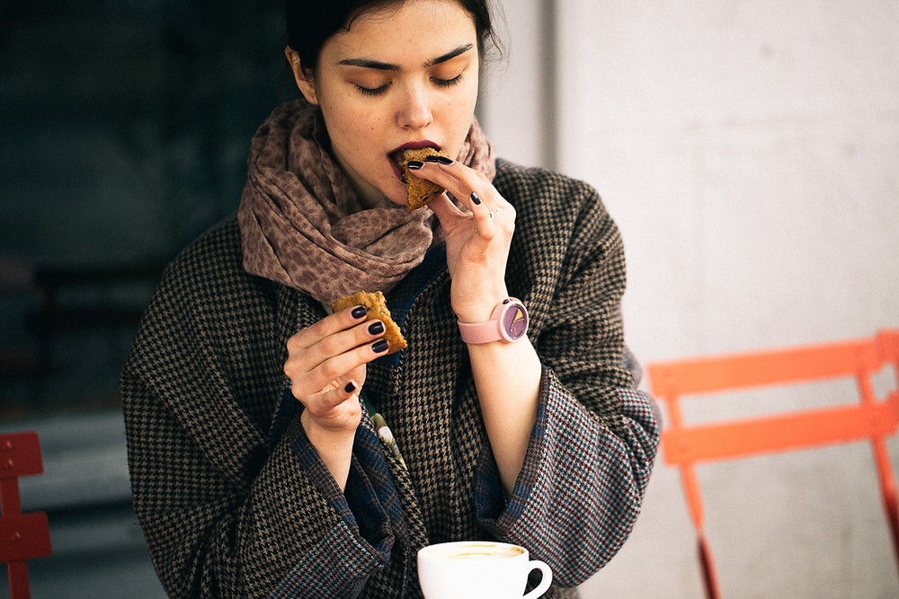 woman sitting and eating a cookie with her eyes closed