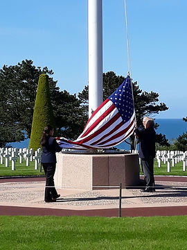 Lowering the flag at Colleville cemetery