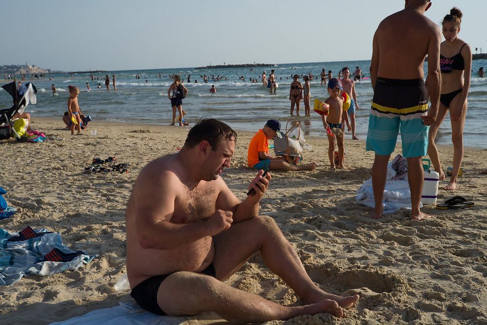 מתרחץ מסתכל בטלפון בחוף פרישמן. קורס צילום בירק