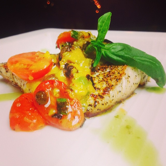 Halibut served with a kumquat sauce, cherry tomatoes and fresh basil leaves