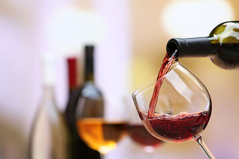 Red wine pouring into wine glass, close-
