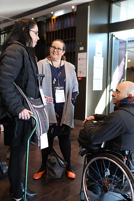 Image description: Morwenna smiling and speaking with other delegates and presenters at the Arts Activated Conference, 2019