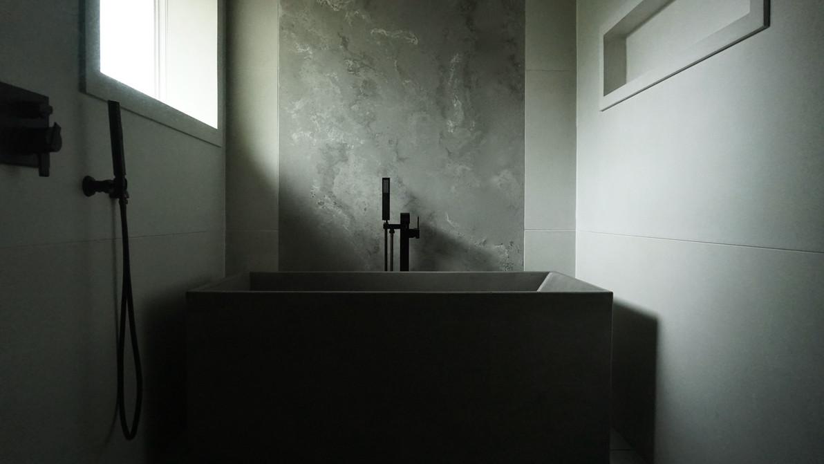 Wet Area with Concrete Bathtub, Concrete Nooks, & Concrete Wall Panels In Natural Light