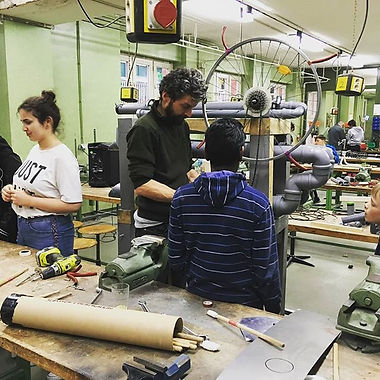 In einer Schulwerkstatt baut Sascha mit Kindern ein Instrument aus Rohren und einer alten Fahrradfelge