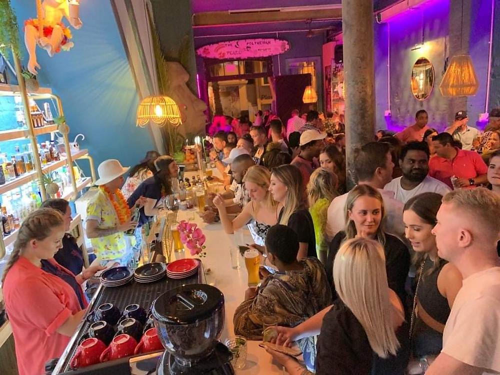 Patrons enjoying a vibey tiki bar, a fresh dose of escapism