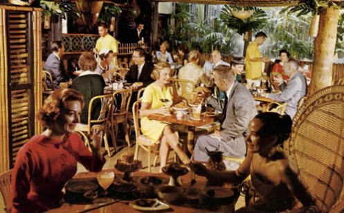 A full tropical style restaurant, with vibrant people eating and drinking in a social setting. Circa 1960's