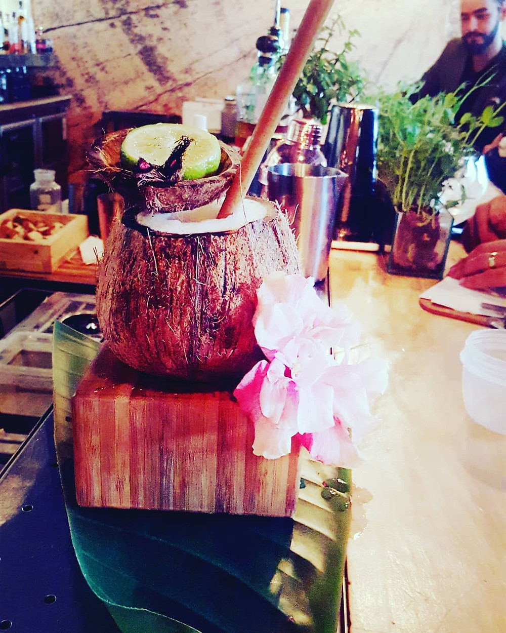 A tiki cocktail in a coconut with elaborate garnish