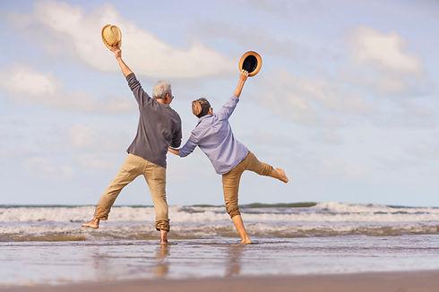 asian-senior-couple-jumping-beach-elderl
