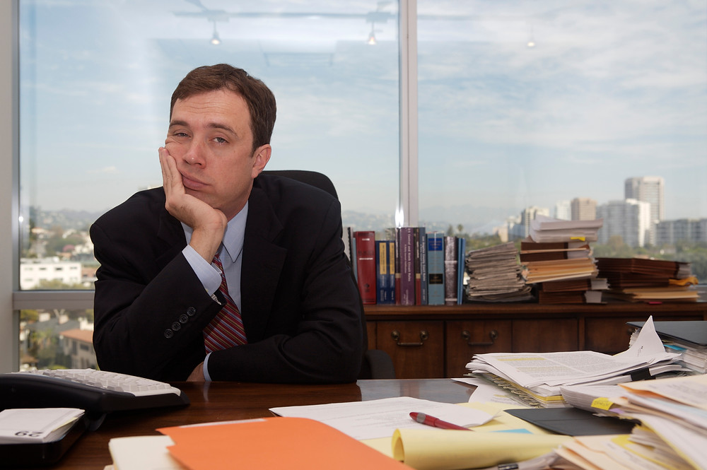 Bored business man sitting at desk covered in papers with city skyline behind him