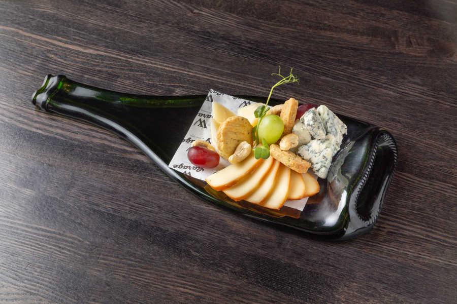 Бутылка сыра с розмариновым печеньем, виноградом и орешками