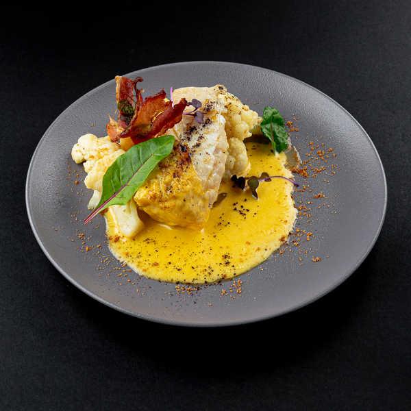 Филе трески с цветной капустой, чипсами из бекона, огуречным пеплом, облепиховой крошкой и голландским соусом