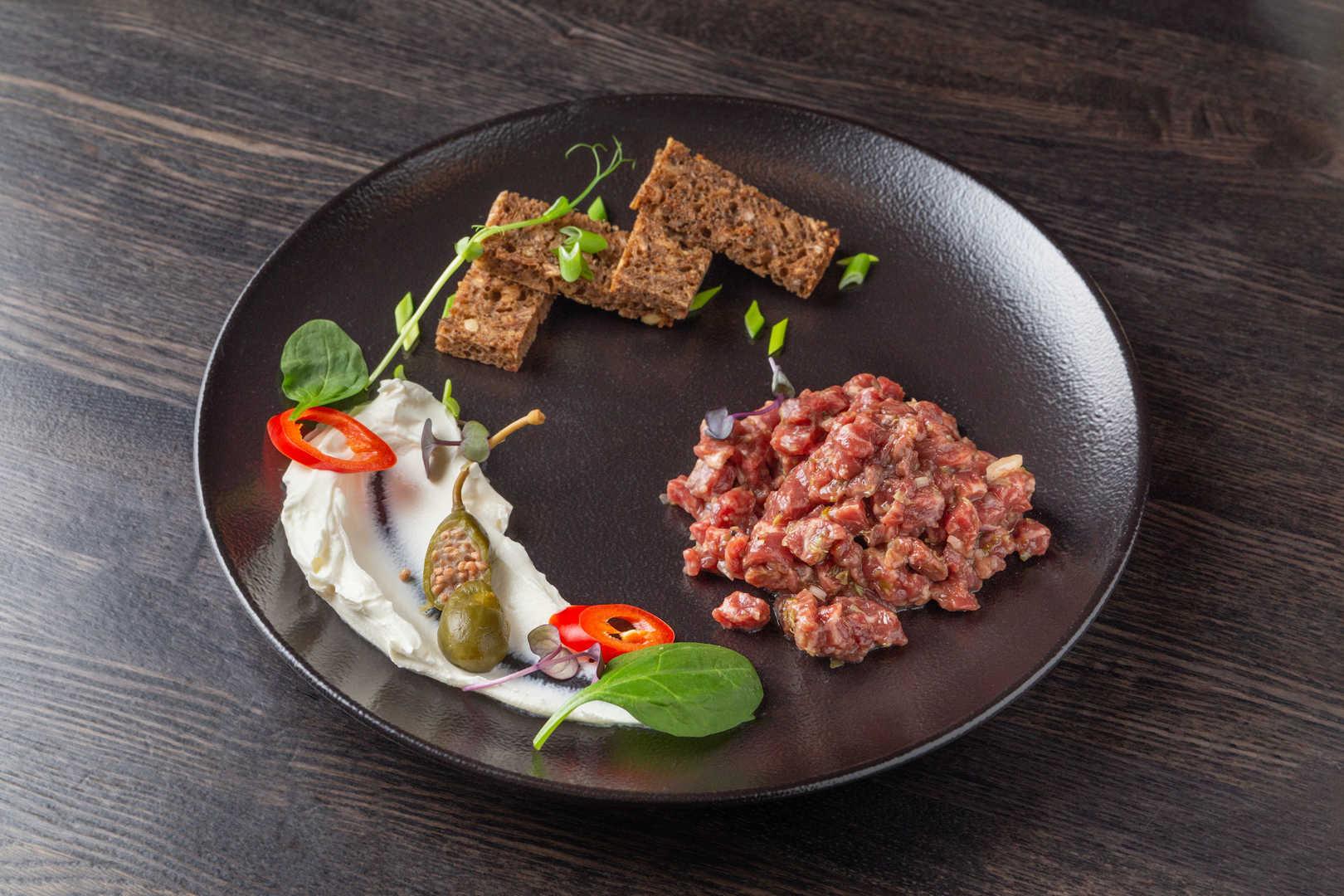 Тартар из говядины с сырным кремом, гренками и ябдочным дымом