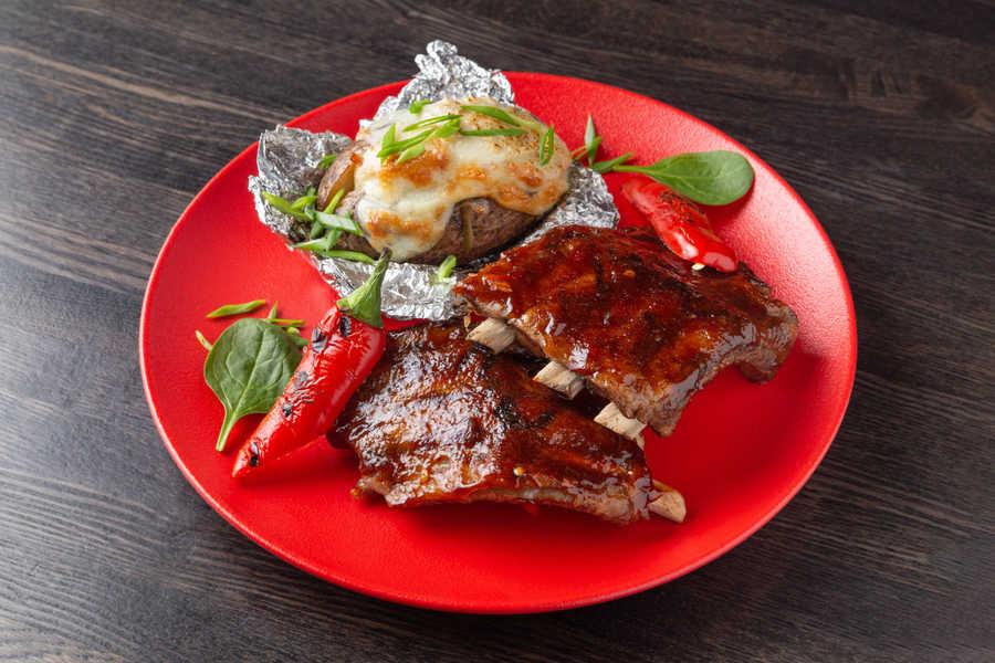 Томленый свиные ребрышки и запеченный картофель со сливочным соусом и беконом