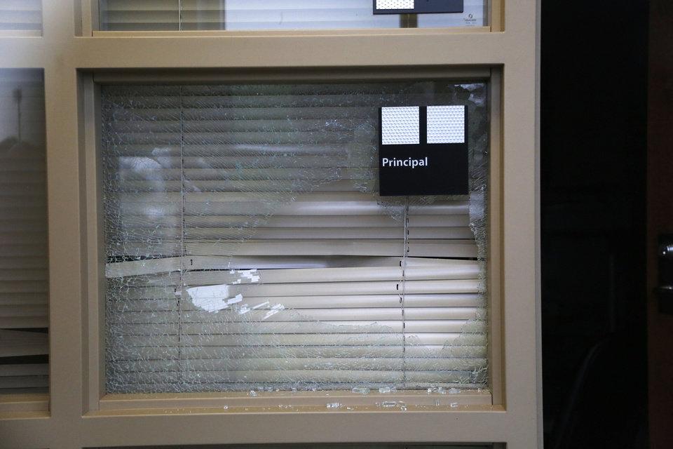 Broken window in a school, causing security risk.