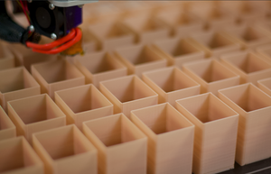 many of the same  square tan part on the bed of a commercial 3D printer