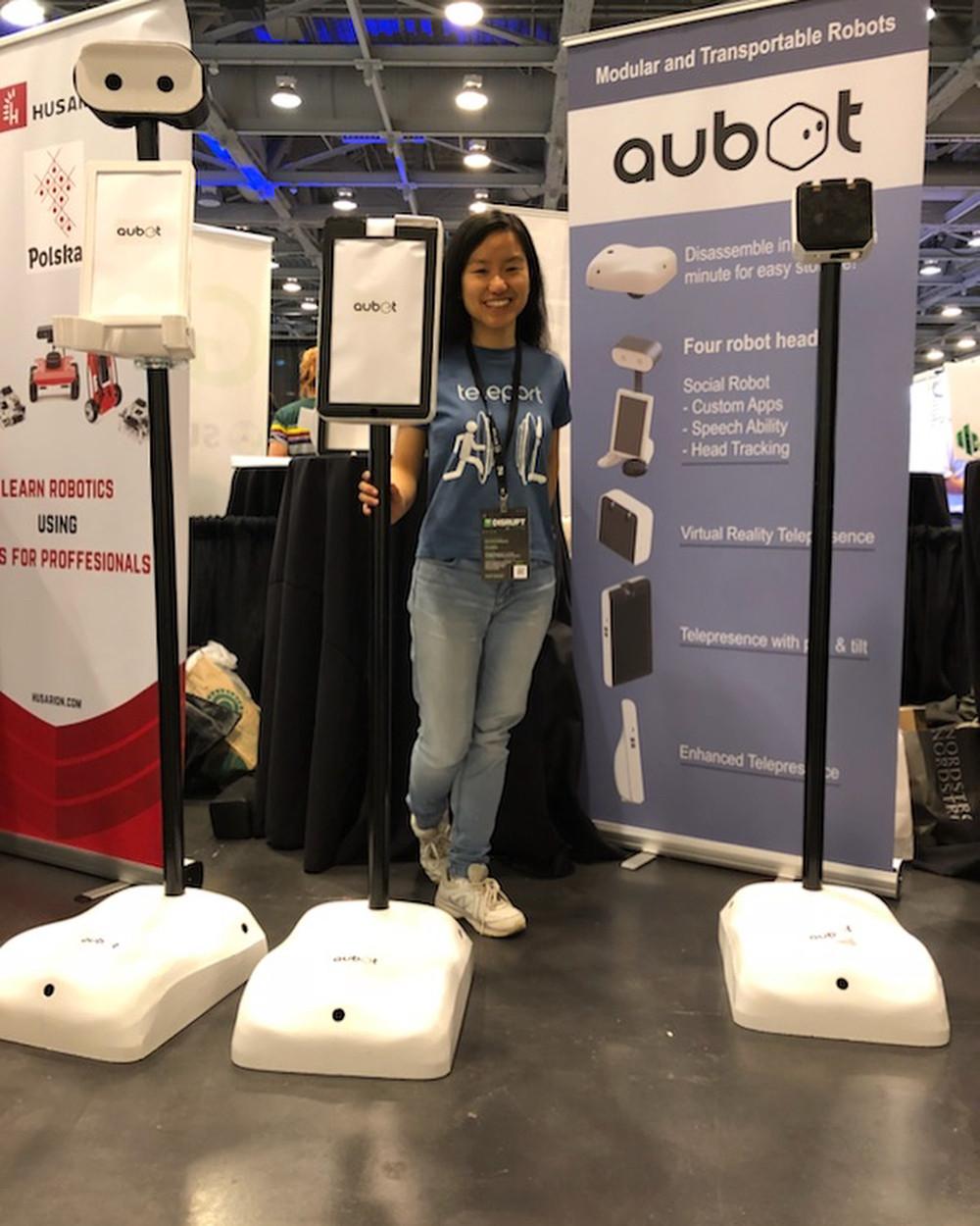 A women standing next to the aubot robot replicas at a trade show