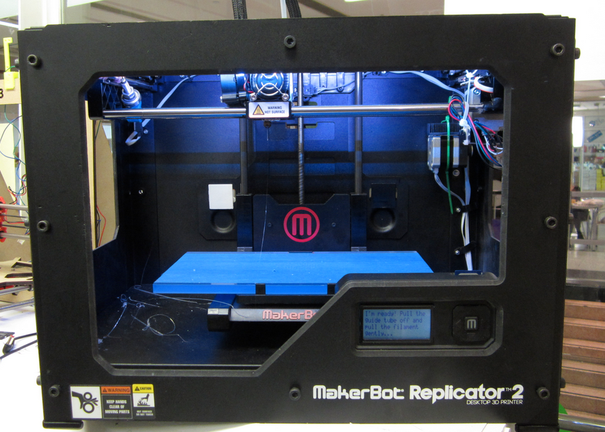 A maker bot replicator 2 on a table in a workshop