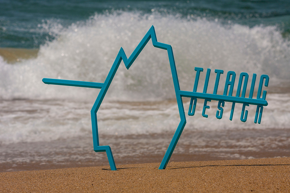 The Titanic Desing logo stuck in the sand at a beach with a wave crashing behind it