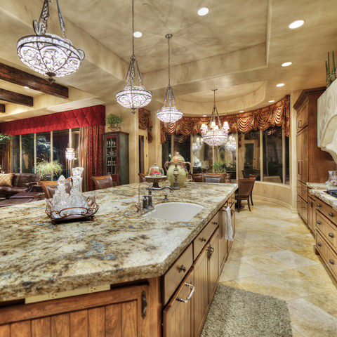 Crystal chandeliers are a nice contrast to the massive granite slab in this chef's kitchen. It's nice to balance feminine and masculine design features.