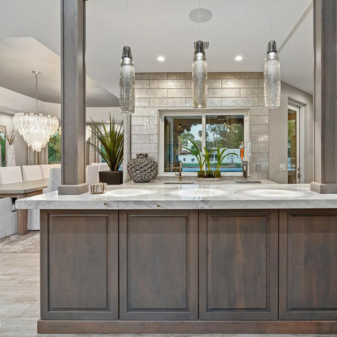 Notice the glam backsplash tile goes all the way up to the ceiling. Three pendant lights were the perfect choice to illuminate this beautiful countertop on this bonus island. It was designed to be used as a bar, but it could also double as a buffet when entertaining or for additional prep space.