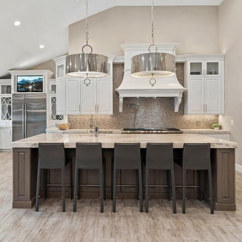 Counter height islands are much more functional than the two-leveled ones of the past. Counter seating can be a focal point in some kitchens, but in this case the simple lines on these leather stools allow this beautiful kitchen to shine.