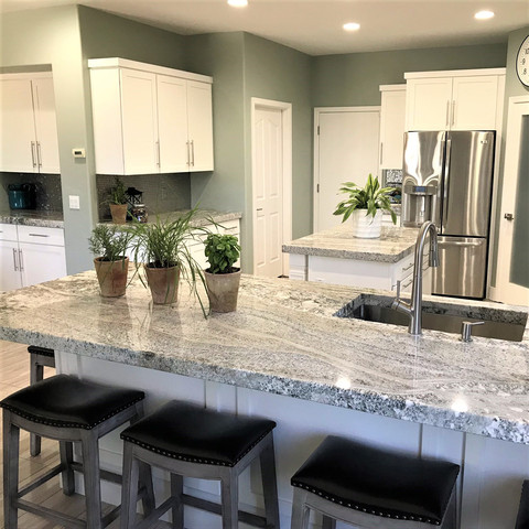 Gorgeous quartzite slabs steal the show in this kitchen remodel.  Tip 1: Ask the fabricator add the thick edge profile to the inside edge of the sink. Tip 2: Don't shop for slab remnants outdoors in July in Arizona. Trust me on this!