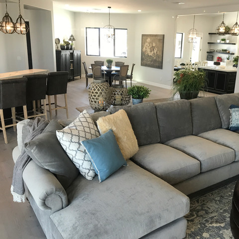 This oversized sectional invites you to sit and stay awhile. Behind it you will notice the same light fixtures were selected for the bar area and kitchen island. To add variety and interest, we sourced an iron birdcage-shaped chandelier for over the kitchen table and a large orb shaped chandelier for the dining table.
