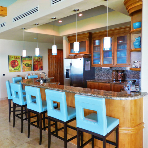 Blue leather bar stools add a pop of color to this kitchen at the beach. The accent color is repeated in the series of pendant lights and on the ceiling.