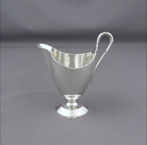 An English sterling silver cream jug by Omar Ramsden, London 1935