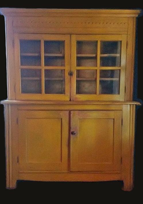A unique Ontario pine glazed step back ochre cupboard, second quarter 19th C