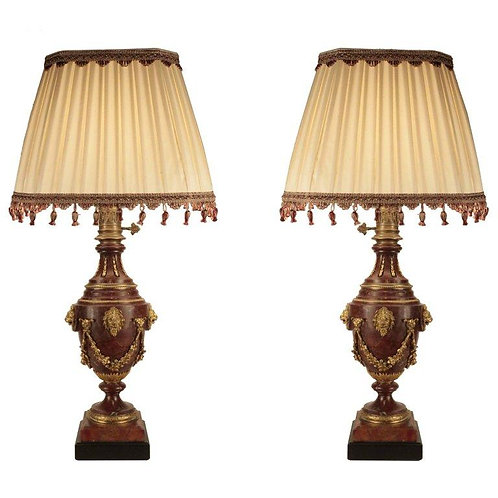 A pair of rouge marble and gilt bronze baluster shaped oil lamps