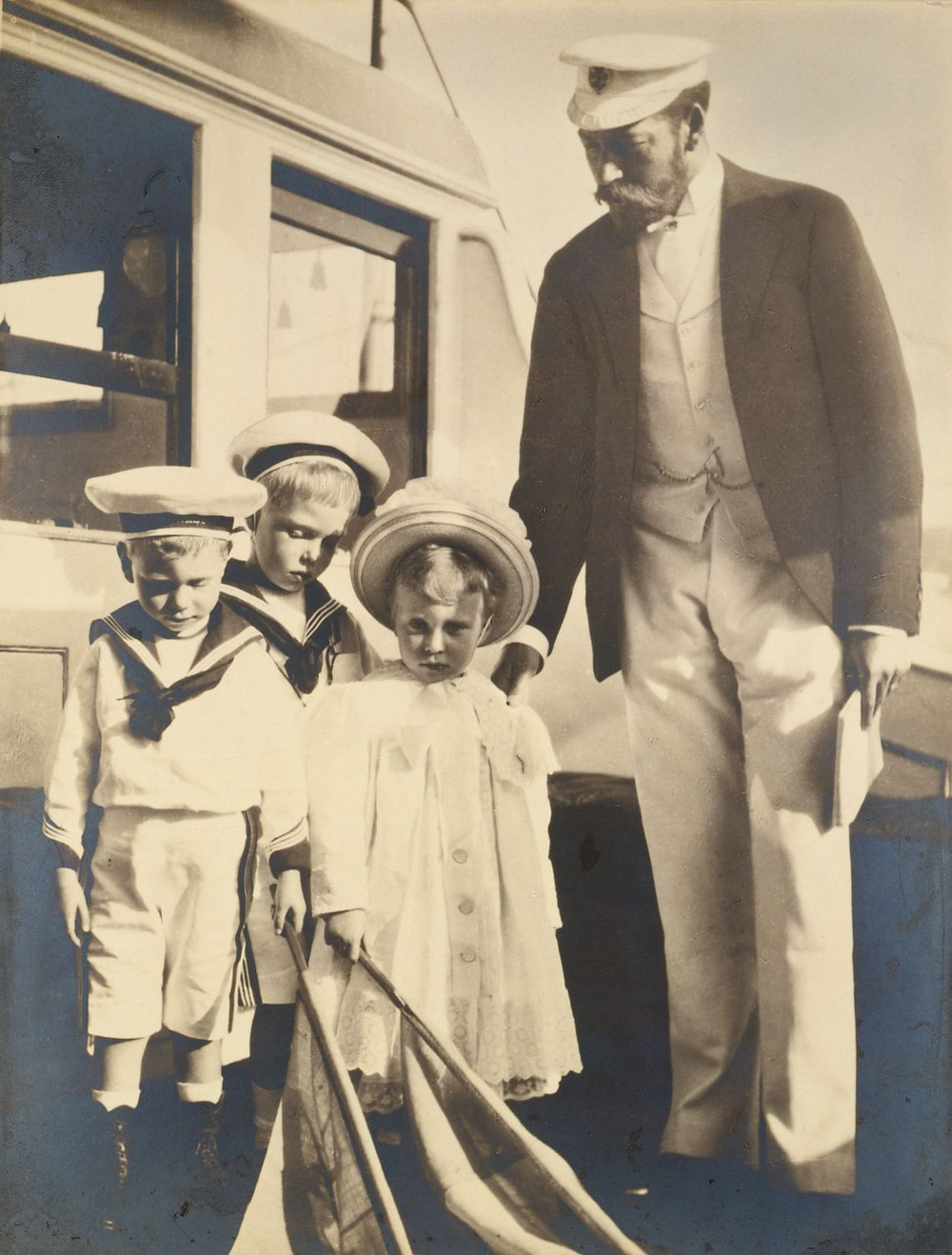 George, Duke of York (later George V), & his children Prince Albert (later George VI), Prince Edward (later Edward VIII) & Princess Mary, on board HMY 'Osborne' Aug 1899. Royal Collection Trust/(c) Her Majesty Queen Elizabeth II 2019