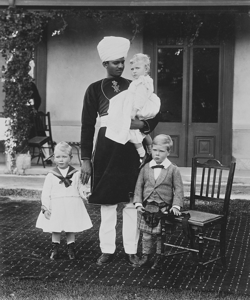 Left to right: Prince Albert, standing in sailor dress; Sheik Abdullah holding Princess Mary in his arms; and Prince Edward, standing in Highland dress.