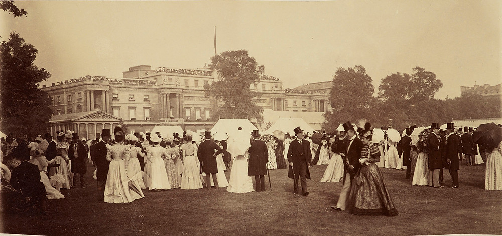 A photograph taken during a garden party at Buckingham Palace for Queen Victoria's Diamond Jubilee. The photograph shows the West facade of Buckingham Palace in the background with crowds of ladies and gentlemen in the foreground in the garden. from the Royal Collection