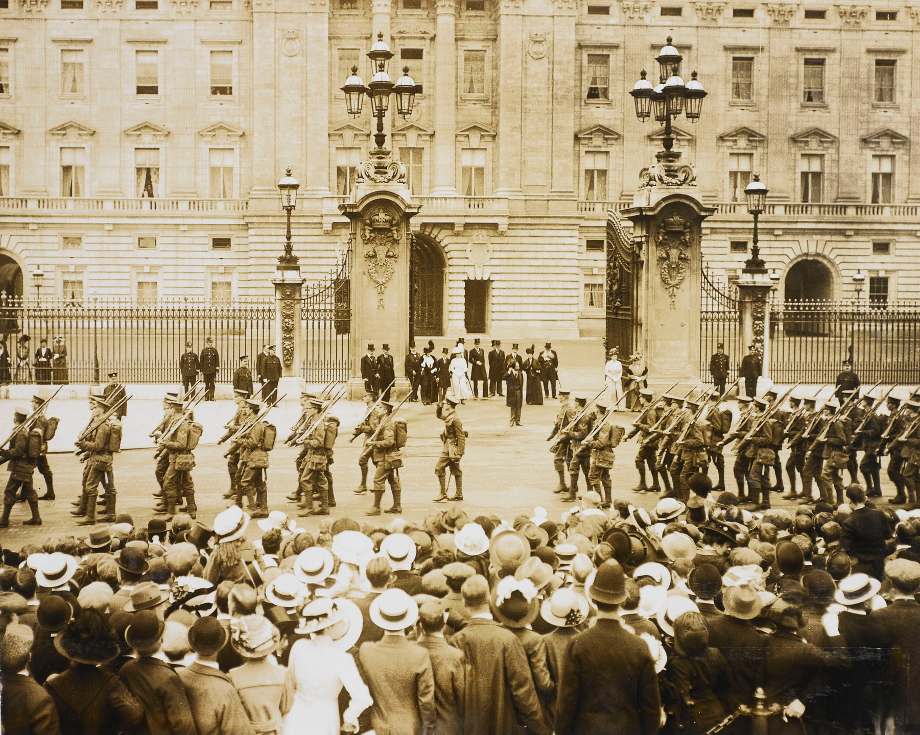 2nd Battalion Grenadier Guards before departure for Front 9 - 9 Aug 1914. Photograph showing the 2nd Battalion of the Grenadier Guards parading in front of the Royal Family who stand at the gates of Buckingham Palace with some Royal Household officials. The King is seen holding his hat next to his head, taking the salute from the troops marching towards the left of the image. Crowds are in foreground. The photograph is from an album compiled by Queen Mary and bearing annotations in her own hand.