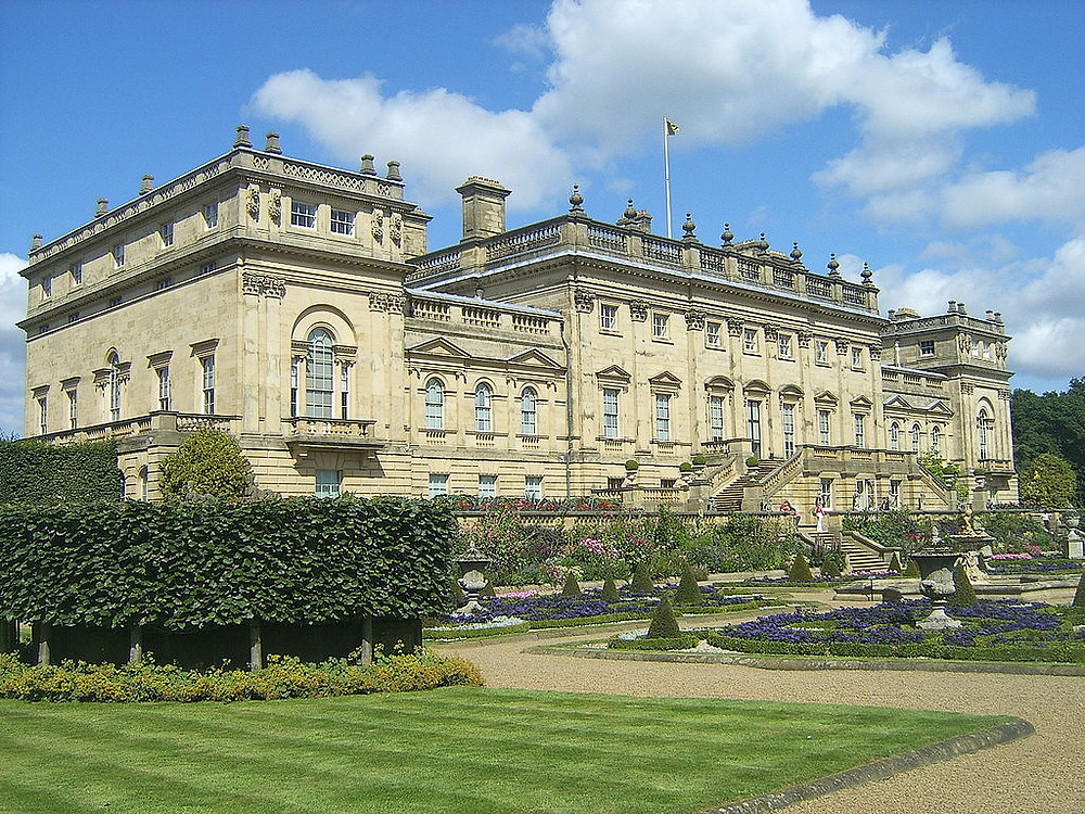 """Harewood House is a country house in Harewood near Leeds, West Yorkshire, England. Designed by architects John Carr and Robert Adam, it was built, between 1759 & 1771, for Edwin Lascelles, 1st Baron Harewood. The landscape was designed by Lancelot """"Capability"""" Brown & spans 1,000 acres (400ha) at Harewood. Still home to the Lascelles family, Harewood House is a member of the Treasure Houses of England, a marketing consortium for ten of the foremost historic homes in the country. The house is a Grade I listed building & a number of features in the grounds & courtyard have been listed as Grade I, II and II*. photograph of Harewood house"""