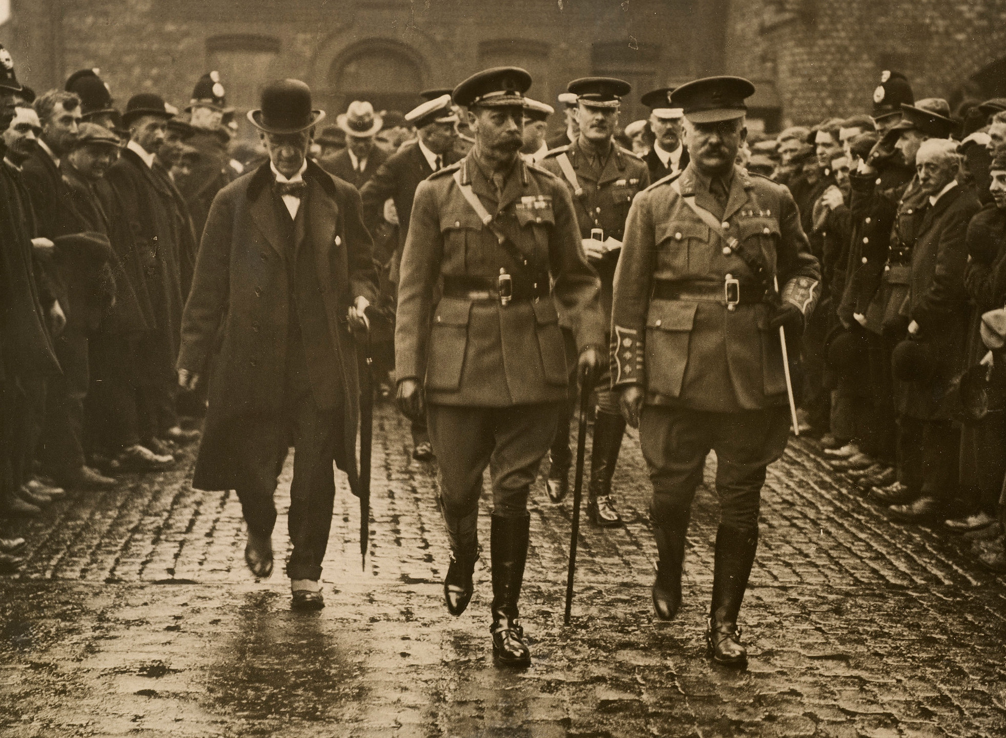 Photograph of, from left to right, Sir H Robertson (1841-1919), King George V (1865-1936) and Colonel H Concanon (1861-1926) walking towards the camera followed by army and navy officers and civilians. Crowds of people stand either side of the group. The three men are visiting the White Star Line Docks.. Royal history, British history, the Great war