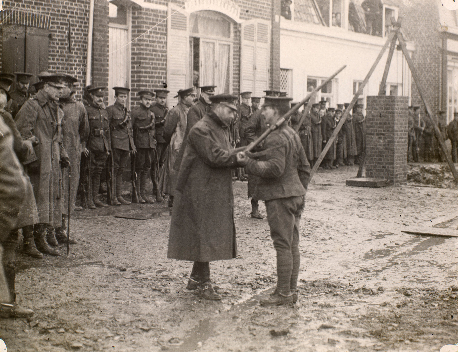 King George V  in uniform and coat pinning a medal to the chest of a Sergeant from the 1st Division. The Sergeant holds a rifle over his left shoulder. The action takes place on a muddy street lined with buildings. A line of soldiers stand in the background.