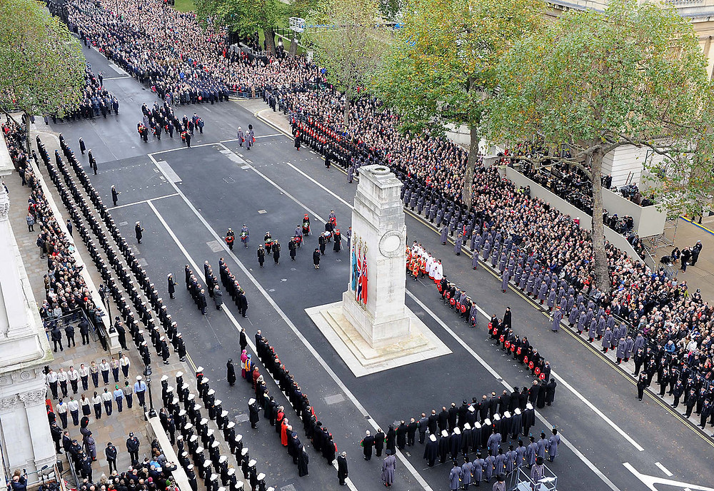 Her Majesty the Queen steps back to pay her respects after laying a wreath at the Cenotaph in Whitehall, London, during the Remembrance Sunday service. source: Photo: POA(Phot) Mez Merrill/MOD [OGL (http://www.nationalarchives.gov.uk/doc/open-government-licence/version/1/)], via Wikimedia Commons