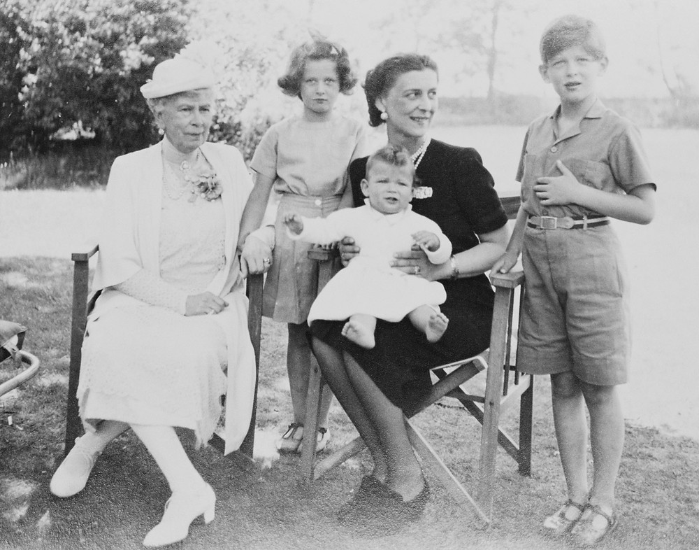Photograph of Queen Mary (1867-1953) with the Duchess of Kent (1906-68) and her children, Edward, Duke of Kent (b. 1935), Princess Alexandra (b. 1936) and Prince Michael of Kent (b. 1942), sitting on his mother's lap; sitting in a garden, during summer, 1943. Royal Collection Trust/(c) Her Majesty Queen Elizabeth II 2018