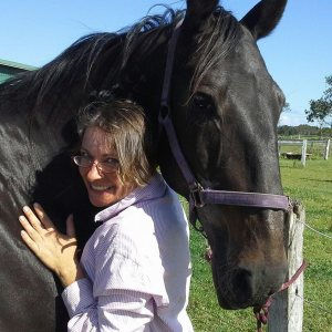woman smiling with a huge black horse