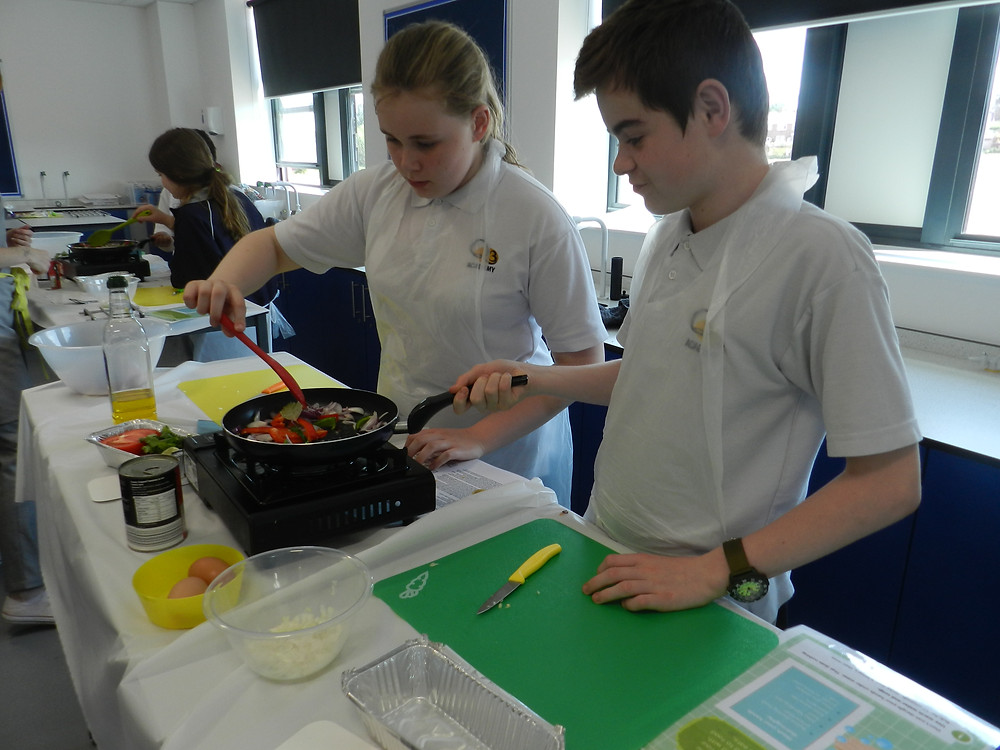 Students cooking their vegetables for the Hueveos Rancheros sauce