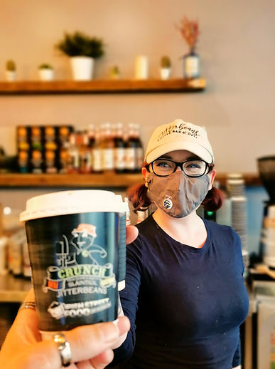 Jitterbeans staff with mask smiling and passing a coffee cup