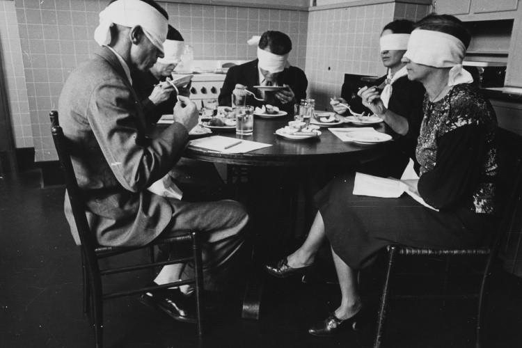 Blindfolded focus group in mock kitchen taste testing meats in 1935.