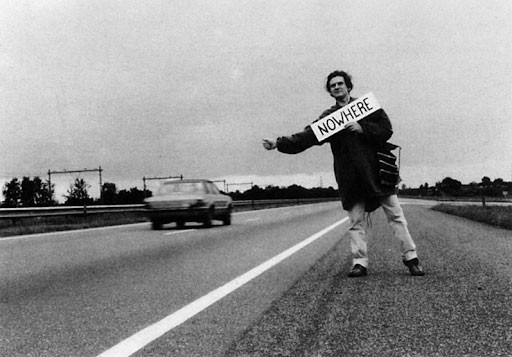 "Man hitchhiking on road with a sign that says ""Nowhere"""